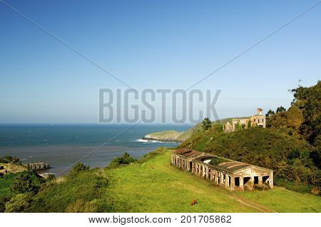 Picturesque Landscape with Abandoned Buildings over Horizon Sea on Blue Sky background Outdoors. Cabo de Penas Asturias Spain