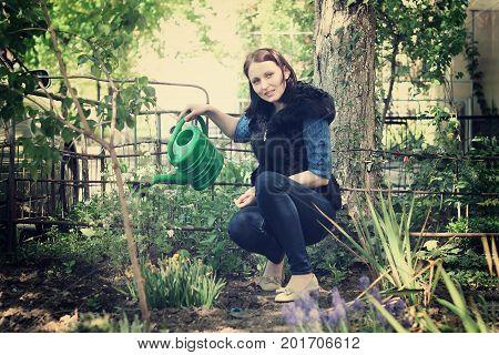 Positive casual dressed girl in yard gardening waters flowers