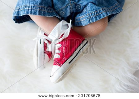Fashionable Red Sneakers On Little Newborn Baby Boys Feet