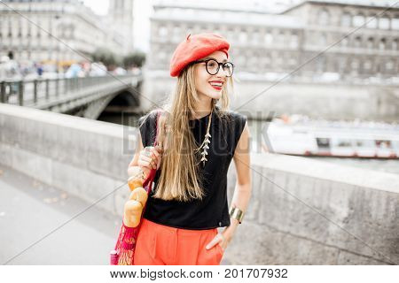 Young stylish woman in red cap walking with mesh bag full of french food on the street in Paris