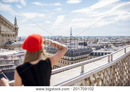 Young woman in red cap standing on the terrace with great cityscape view with Eiffel tower in Paris. Woman is out of focus