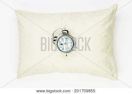 Retro Alarm Clock On The Soft Feather Pillow Close-up On A White Background