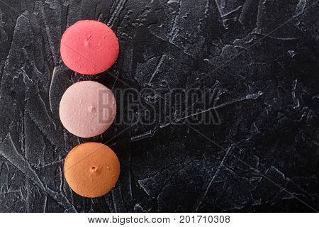 Classic French Macaroon cookies pink and orange on black concrete background