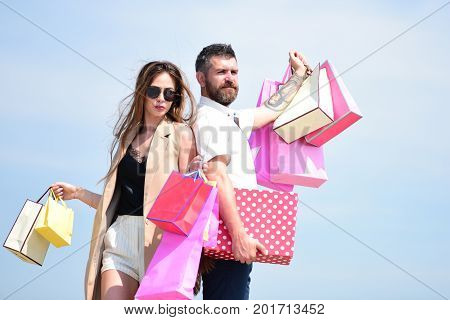 Sexy girl and guy with confident faces make purchases. Couple carries pink packets and box on blue background. Shopping and shopaholism concept. Man with beard and long haired woman hold shopping bags