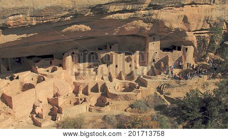 A group of tourists on a tour of the ancient Cliff Dwellings of Mesa Verde National Park
