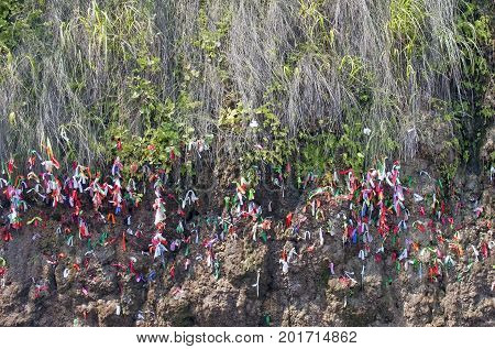 pieces of colored tissue a large number of colorful scraps of fabric tied to the branches of trees on a rock a ritual to bind the pieces of colorful cloth on tree branches