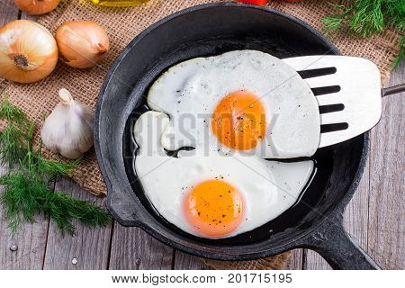 Fried eggs with spatula in frying pan