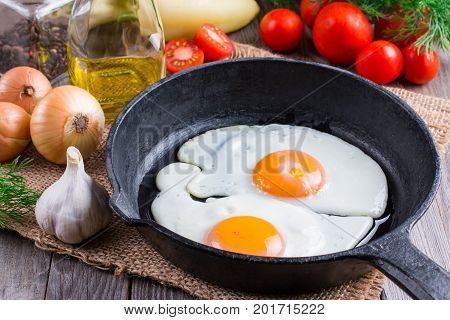 Fried eggs in a frying pan on a wooden background