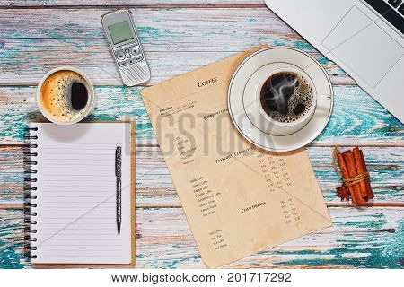 Taking interview in cafe during coffee break. Two cups with different varieties of coffee on the table with rough loft style surface laptop dictaphone and sketchbook in horizontal top view.