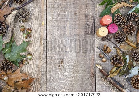 Rustic Wooden Background With Autumn Candles, Leaves, Acorns, Pinecones And Branches On Left And Rig