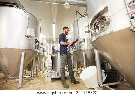 production, business and people concept - men with clipboards working at craft brewery or non-alcoholic beer plant