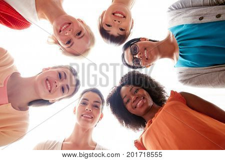 diversity, race, ethnicity and people concept - international group of happy smiling different women standing in circle over white