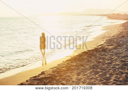 Relaxed woman enjoying sun freedom and life an beautiful beach in sunset.