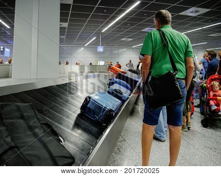 FRANKFURT GERMANY - AUG 8 2017: Exhausted passengers commuters waiting to claim the baggage luggage at modern airport looking at the luggage conveyor belt for their suitcase bag backpack
