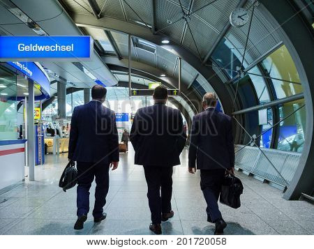 FRANKFURT GERMANY - AUG 8 2017: Rear view of three executive businessmen walking toward the end of the international airport terminal to take the plane for the upcoming business meeting