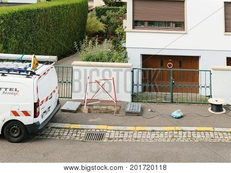 PARIS FRANCE - JUL 12 2017:Open sewage manhole hole with cable on coil spool - telecommunication internet provider company working on implementation of fiber optic cables in sewage system using fiber optic welding machine