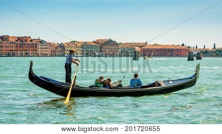 Venice, Italy - May 18, 2017: Gondola with tourists floats along the Grand Canal. Gondola is the most attractive tourist transport in Venice. 16:9 widescreen.