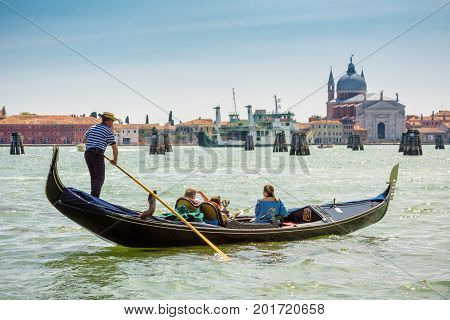 Venice, Italy - May 18, 2017: Gondola with tourists floats along the Grand Canal. Gondola is the most attractive tourist transport in Venice.