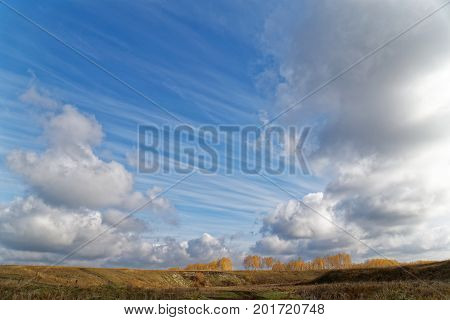 A blue sky with clouds over a autumn landscape with trees in the distance far away in haze
