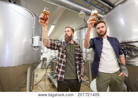 production, manufacture, business and people concept - men testing non-alcoholic or craft beer at brewery