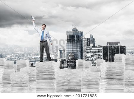 Attractive businessman keeping hand with book up while standing on pile of paper documents with cityscape on background. Mixed media.