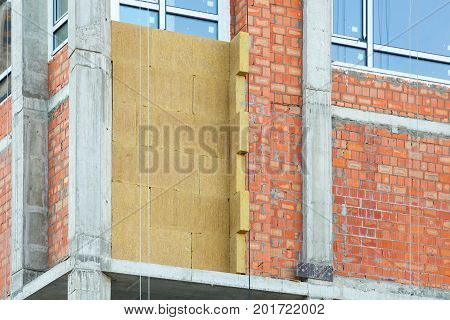 External wall insulation. Solid wall insulation. Energy efficiency house wall renovation for energy saving. Exterior house wall heat insulation with mineral wool building under construction.