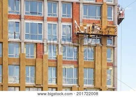 High-altitude work on the external walls of high-rise building. Glass wool insulation. The worker insulates the house standing on the scaffolding