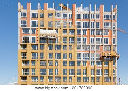 Construction workers insulating house facade with mineral rock wool installation. External wall insulation system (or EWIS) mineral wool for energy saving