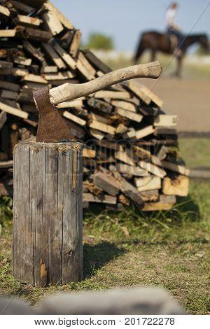 Old axe stuck in stump near woodpile - farm in Russia, telephoto