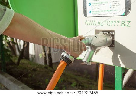 Electric car charging vehicle energy power for environmental friendly. Woman holding charging cable of electric car.