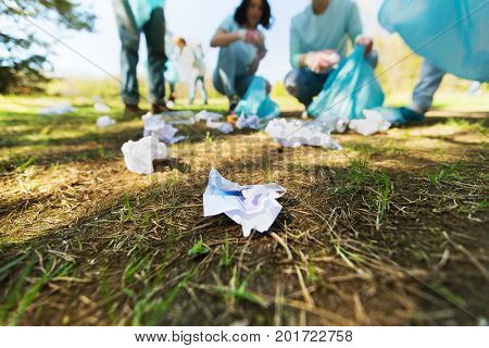 volunteering, people and ecology concept - group of happy volunteers with garbage bags cleaning area in park
