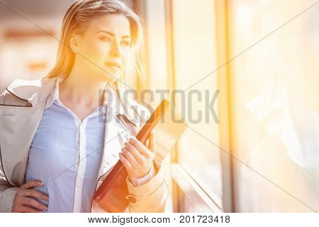 Beautiful young businesswoman looking through glass at railroad station