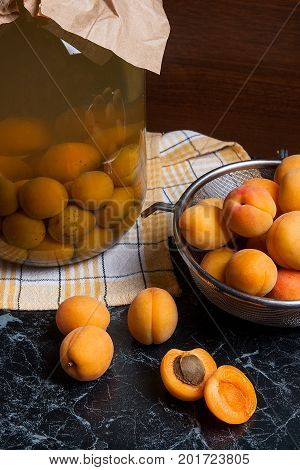 Fresh Organic Harvested Apricots In Steel Colander And Big Glass Jar With Canned Apricot Compote On