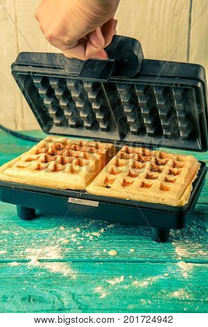 Waffles in waffle iron. Making waffles at home. Cooking background.