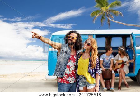 summer holidays, road trip, travel and people concept - smiling young hippie couple with friends in minivan car over beach background