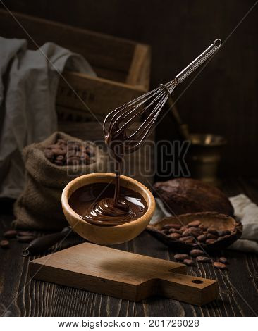 Dark still life with melted chocolate in wooden bowl. Levitation SFX