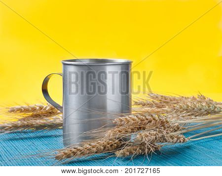 wheat spikelets and metal mug on blue bamboo mat. yellow background