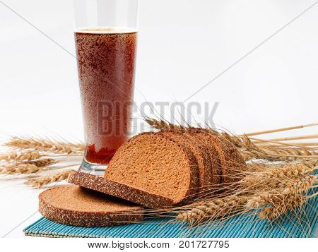 sliced bread and wheat spikelets on bamboo mat with glass of soft drink. selective focus