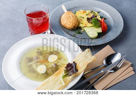 Healthy food background, restaurant business lunch. Noodle soup, vegetable risotto with chicken cutlet, refreshing berry drink on gray table, cutlery and empty business card for copy space