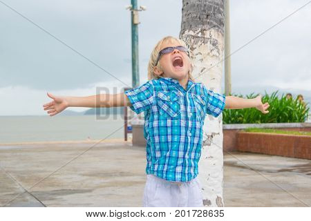 A cool blond boy in sunglasses screeming happyly in a park near beach