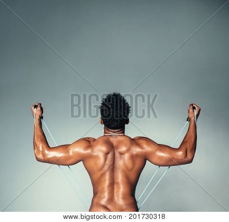 Rear view square shot of fitness male model using stretch band. Young man exercising with elastic band on grey background.