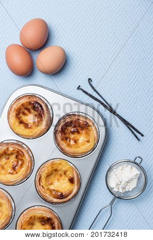 Pasteis de nata typical Portuguese egg tart pastries from Lisbon on a set table. Top view with copy space
