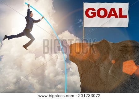 Businessman pole vaulting towards his success goal