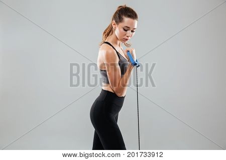 Side view of a confident pretty sportswoman standing and doing exercises with hand expander isolated over gray background