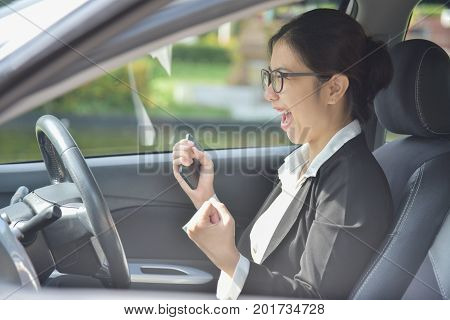 Relaxed Asian Business girl in glasses celebrate with raised hands up in a car. Success and Happy Concept. Smiling face.