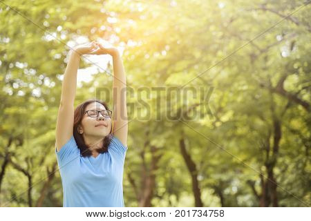 Happy Asian woman with Glasses in Blue shirt breathing deep fresh air and stretching her arms on Green natural background. Girl with Outdoor park. Copy space.