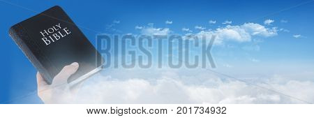 Digital composite of Hand holding bible and sky transition
