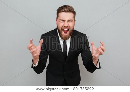 Portrait of an angry bearded man in suit shouting and gesturing with hands isolated over gray background