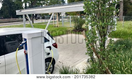 electric car being charged in front of carport covered with solar panels - concept for future sustainable and self-contained mobility