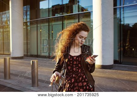 Staying connected. Beautiful European teenage girl wearing leather jacket over floral dress standing at modern glass windows building with her bicycle typing text message on generic mobile phone